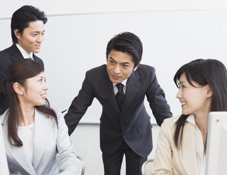 同僚たちに話しかけるスーツ姿の男性