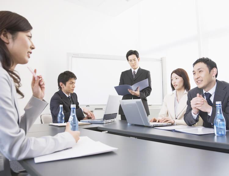 会議室で話し合うスーツ姿の男女5人
