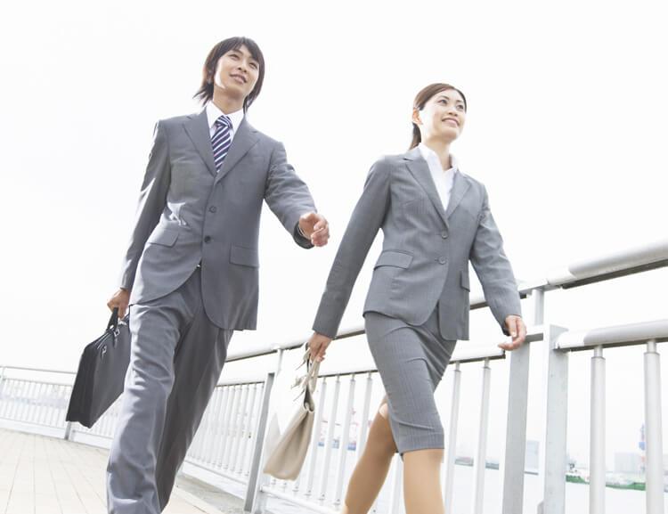 元気に歩くスーツ姿の男女