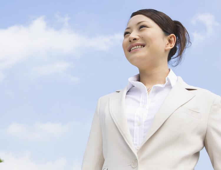 青空の下で微笑むスーツ姿の女性