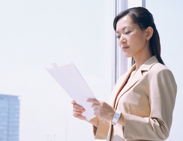 書類を読むスーツ姿の女性